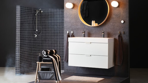 A wall-mounted bathroom cabinet with mirror and lighting in front of which a stool stands