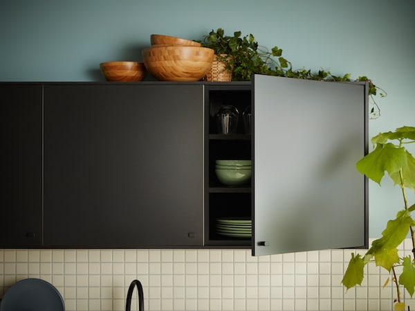 A wall mounted black kitchen cabinet with an open door revealing dishes and bowls.