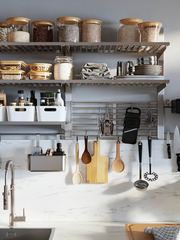 A wall-mounted KUNGSFORS kitchen storage series with glass jars with lids, white VARIERA storage boxes and hanging utensils.