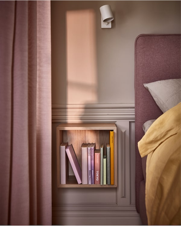 A wall-mounted shelving unit in white stained oak effect, a white wall lamp and walls, a divan bed and curtains in pink.