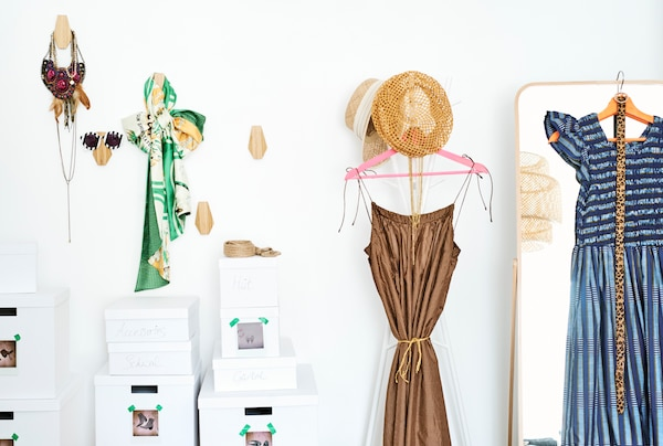A wall of clothes storage with accessories on wooden hooks, shoe boxes, dresses and hats on a coat stand and a long mirror.