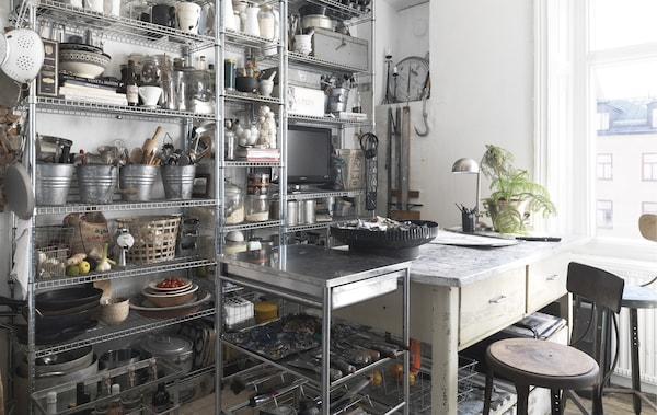 A wall of metal open storage in a kitchen.
