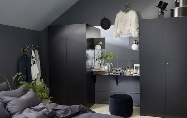 A wall of mirrors and a vanity table between two black-brown PAX wardrobes in a dark, modern bedroom
