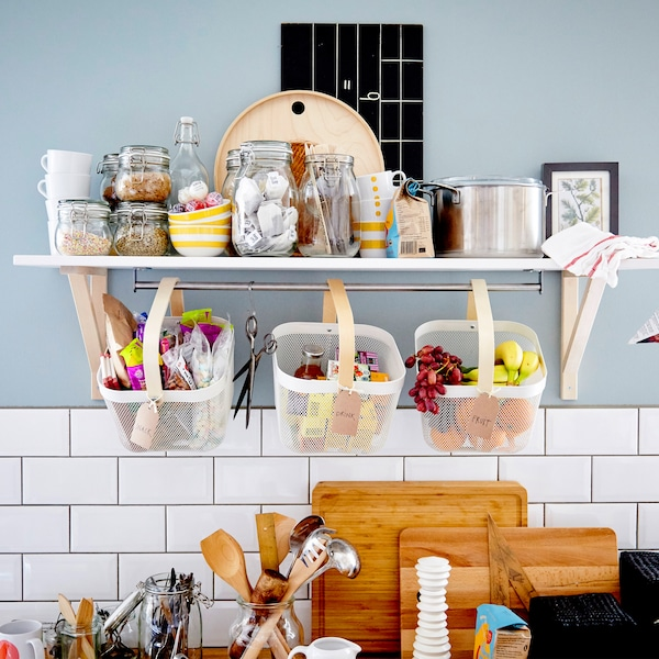 A wall shelf and three baskets filled with containers of dry food stuff and fruit.