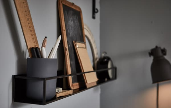 A wall shelf filled with study accessories in a grey room.