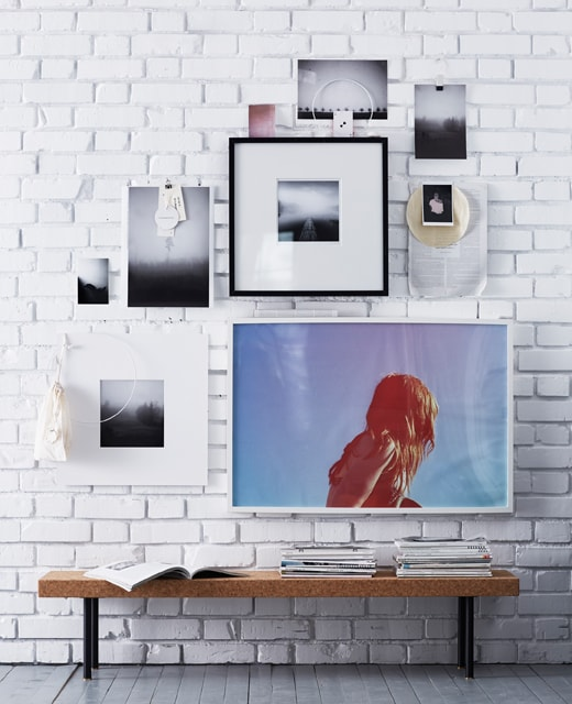 A wall with a combination of poster and photographs with and without frames.