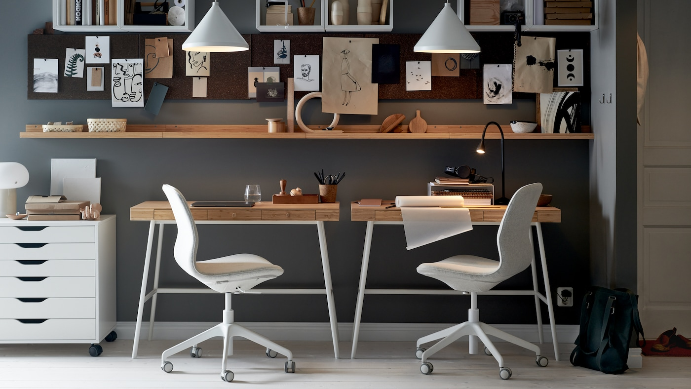 A wall with two LILLÅSEN desks, office chairs and a white drawer unit, with shelving, memo boards and white pendants.