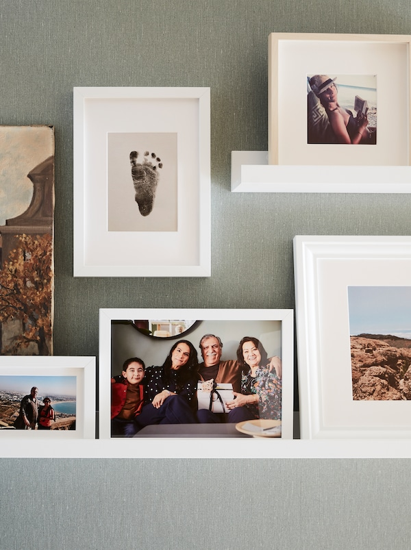 A wall with two white picture ledges and several white RIBBA frames with a baby foot print and family and travel photos.