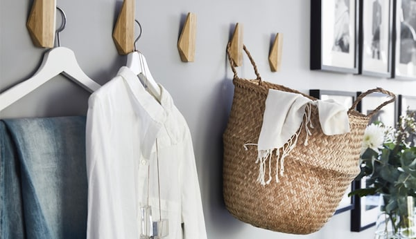 A wall with wooden hooks hanging clothes and a basket.