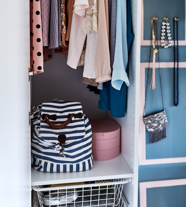 A wardrobe is open to show the clothes and accessories inside.