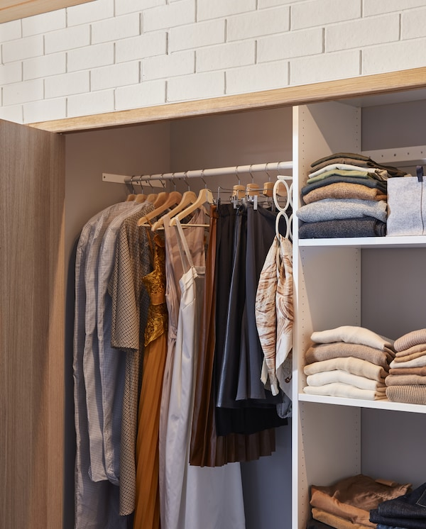 A wardrobe solution that consists of shelves and rails. Some clothes hang on the wooden hangers and some lie on the shelves.