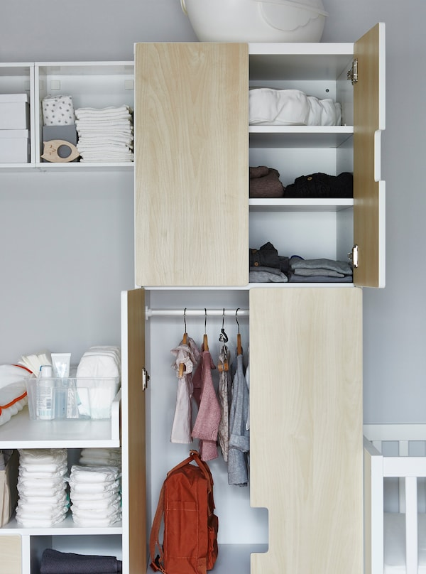 A wardrobe with hanging space for babies clothes.