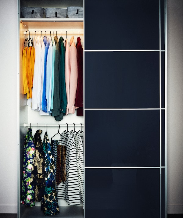 A wardrobe with panelled sliding doors slid to one side, the open half holding two very orderly rows of clothes on hangers.