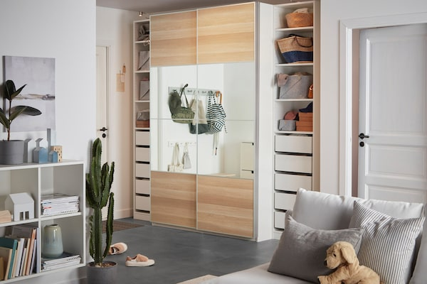 A wardrobe with sliding doors in birch featuring mirror elements and several drawers and shelves.