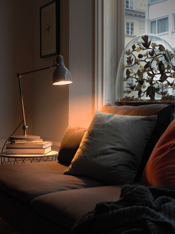 A warm coloured TRÅDFRI lighting by the window is turned on.