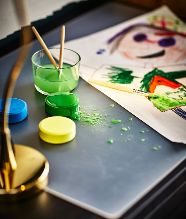 A water color painting is being created at the desk.