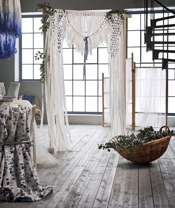 A wedding curtain backdrop made from white cotton fabric strips and greenery tied to a TÄNKVÄRD rattan room divider.