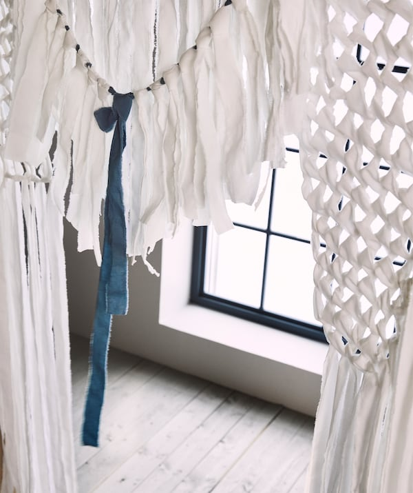A wedding curtain backdrop made from white cotton fabric strips that were tied and knitted loosely like rustic lace.