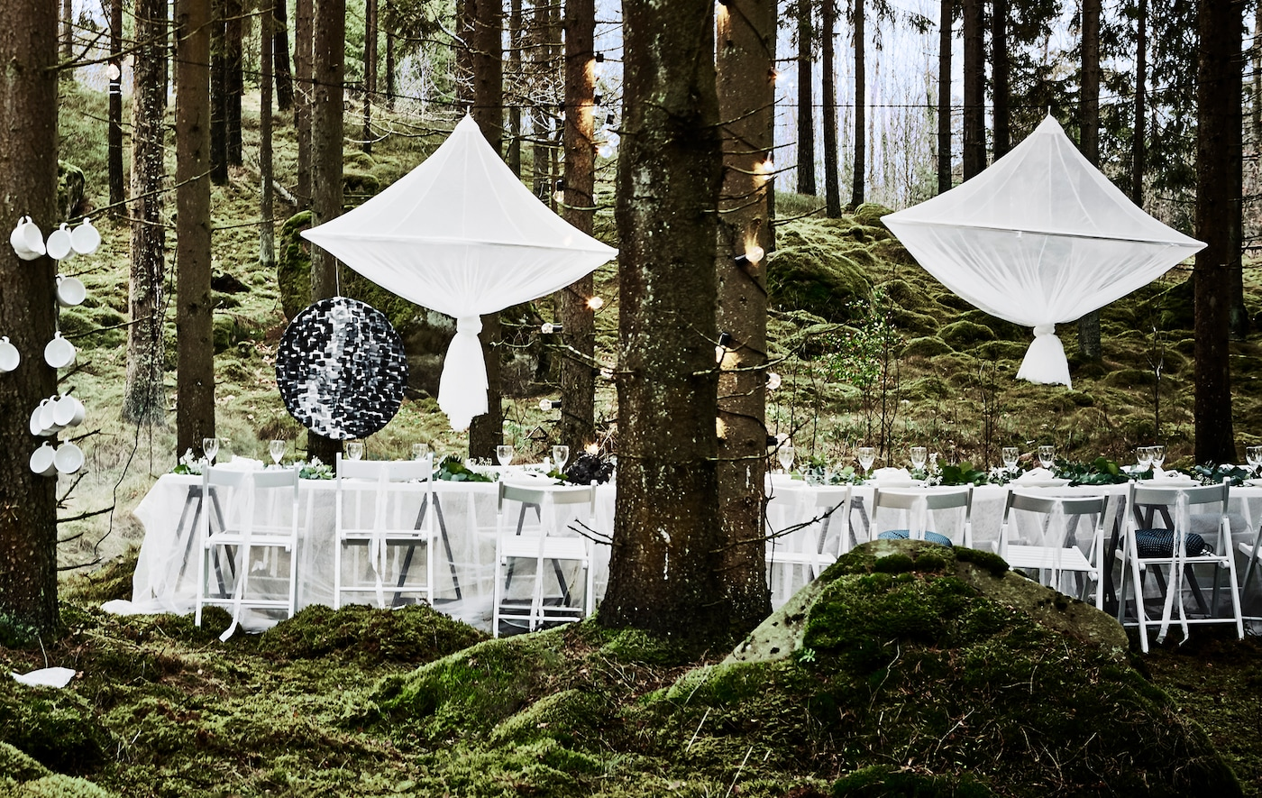 A wedding party dining setup in a forest with white chairs, lace curtain tablecloths and big chandelier-style centrepieces hanging above the table