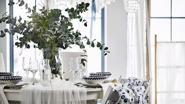 A wedding table with a floral centerpeice, blue fabric backed TERJE chairs with a  white traditional dining set.