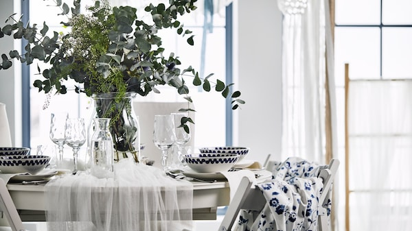 A wedding table with a floral centrepiece, blue fabric backed TERJE chairs with a  white traditional dining set.