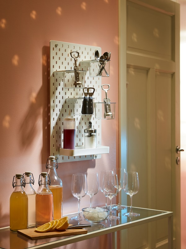 A welcome drink set on a side table. A SKÅDIS pegboard above it holds IDEALISK corkscrews and other accessories.