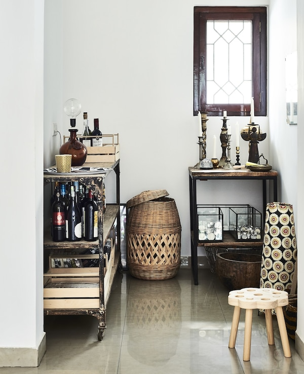 A wheeled trolley and side table in an alcove.