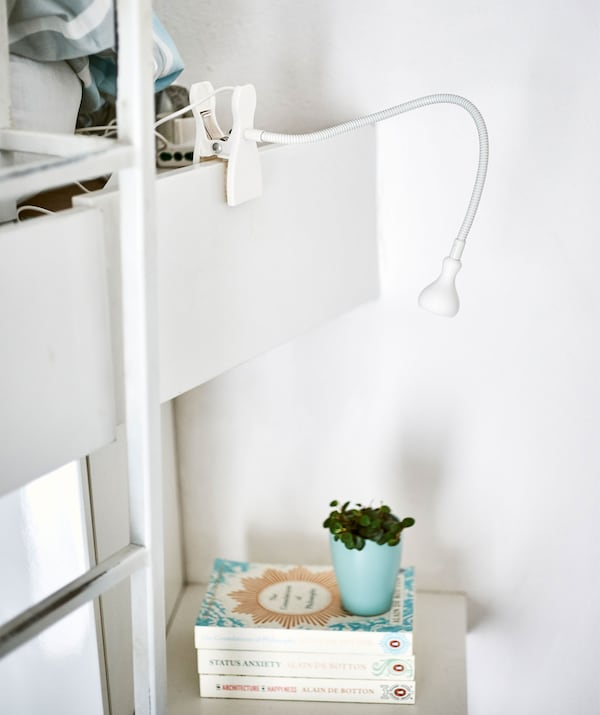 A white adjustable clip-on spotlight pointing towards a stack of books on a shelf.