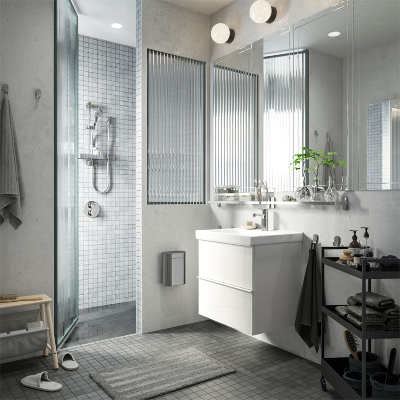 A white and grey bathroom with a shower, a white wash basin and a black trolley that stores towels, soaps and more.