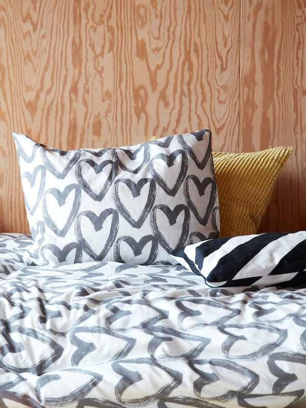 A white and grey LYKTFIBBLA quilt with a heart pattern on lies on a bed in a wood-panelled modern bedroom.