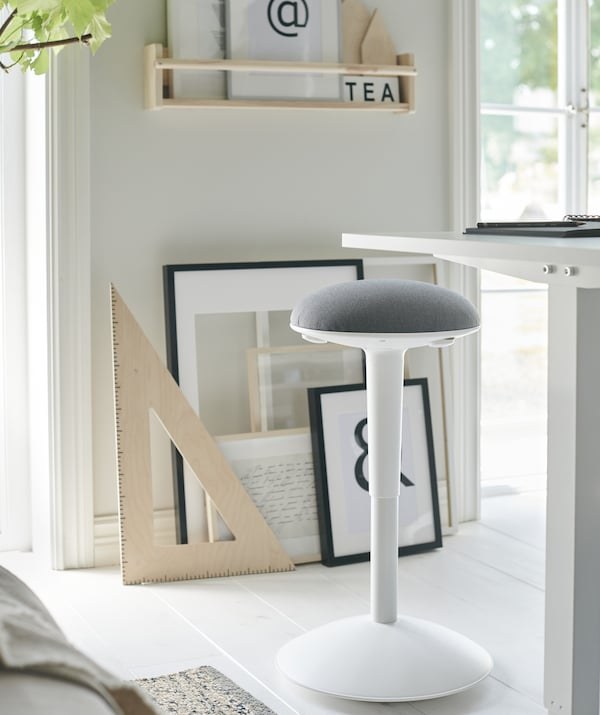 A white and grey stool next to a tall white desk, with artwork leaning against the wall behind.