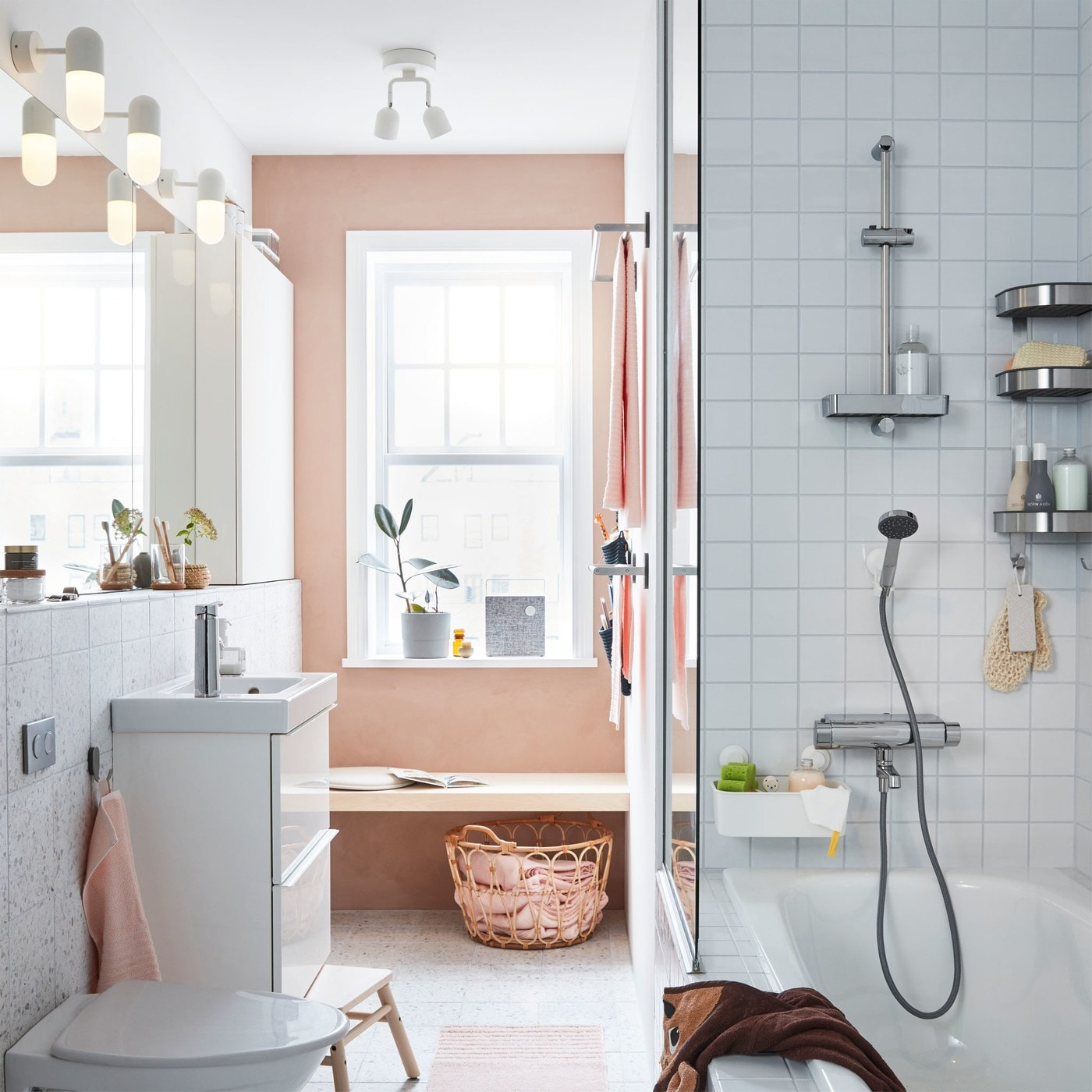 A white and grey tiled bathroom, with a pink accent wall, with an IKEA GODMORGON wash stand and a row of GODMORGON mirrors.