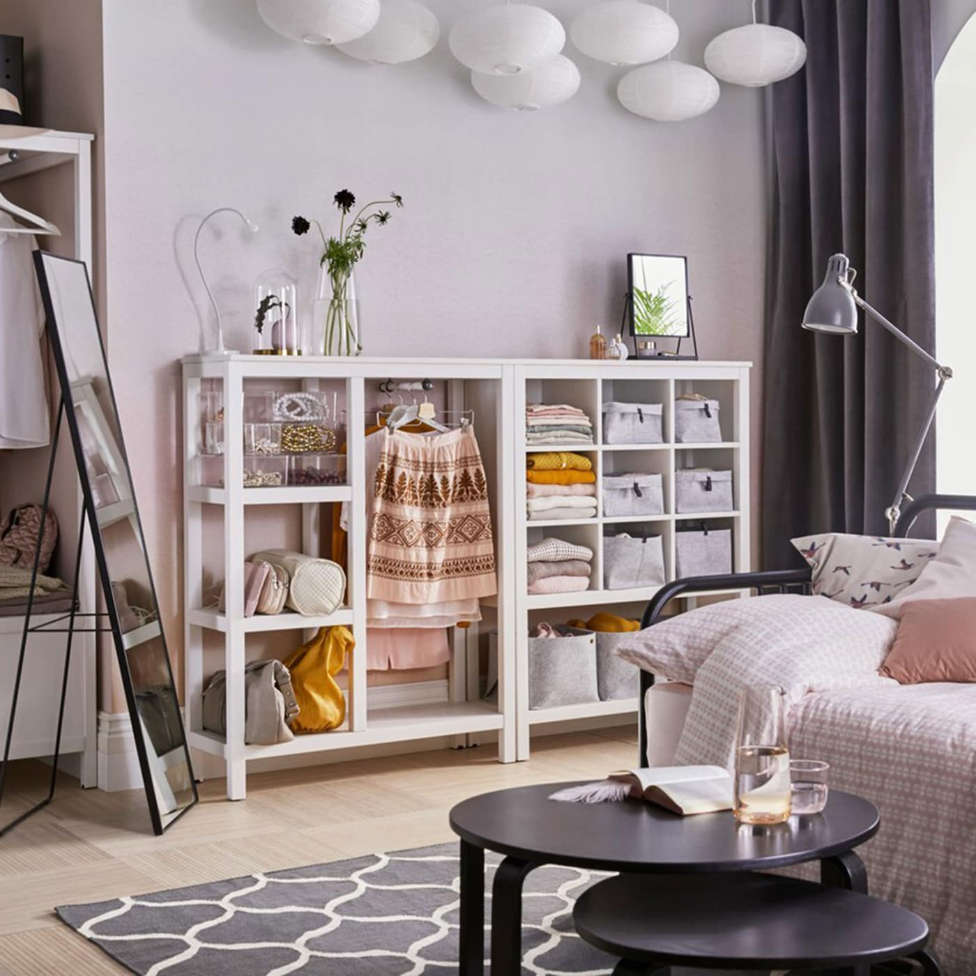A white and pink open space bedroom with white IKEA HEMNES open storage units across the back wall.