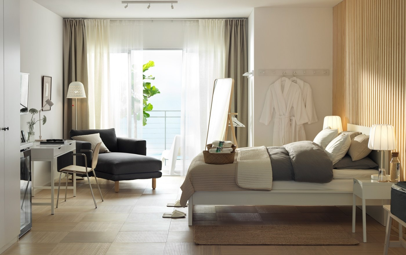 A white and wooden walled hotel room with an IKEA MALM white bedframe, white desk, chaise longues and a sea view.