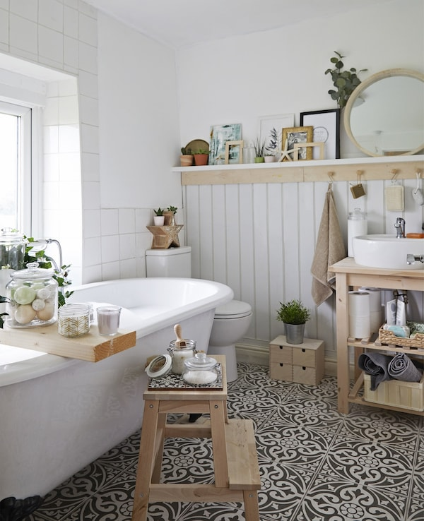 A white bathroom with wooden storage, glass jars and tiled floor.