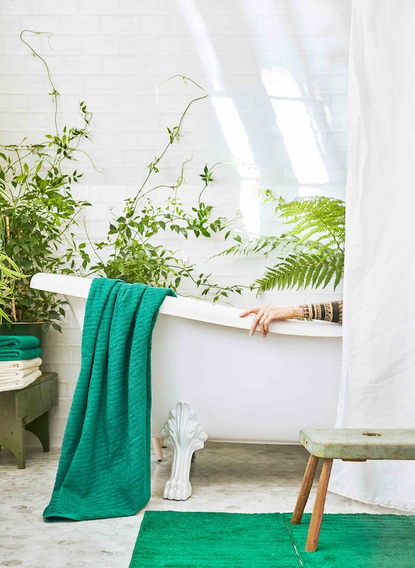 A white bathtub sits in a green plant-filled bathroom, half hidden by a fresh white curtain.