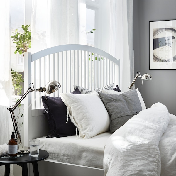 A white bed frame, white curtains, white, grey and black bed textiles and nickel-plated work lamps.