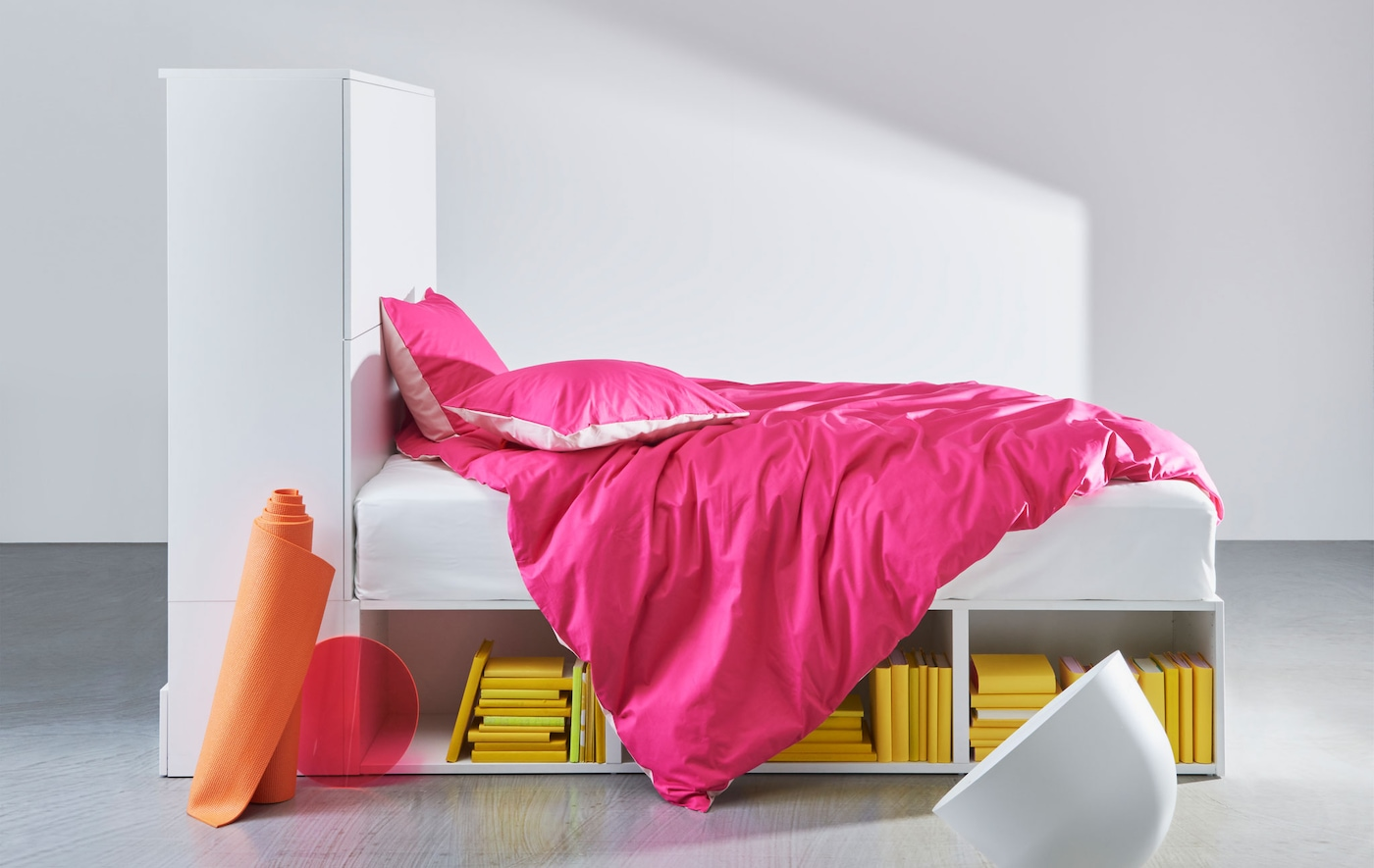 A white bed frame with built-in storage dressed with pink bedding.