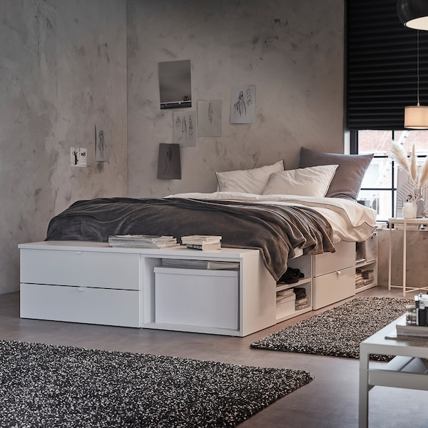 A white bed frame with four drawers, open shelves and a bench. It stands by a window with a dark grey roller blind.
