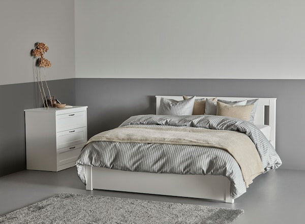 A white bed frame with gray bedding in a room with a white chest of drawers against the wall.