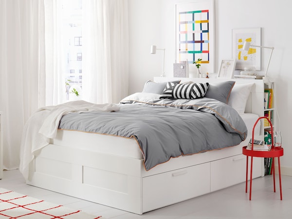 A white bed frame with gray bedding in a room with white curtains, a red side table and a red and white patterned rug.