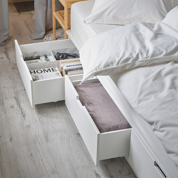 A white bed frame with two spacious, open drawers at the bottom. A pink throw, books, glasses and a watch are stored inside.