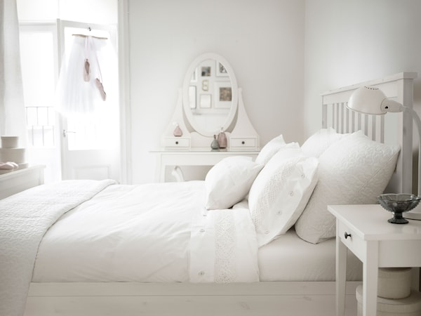 A white bed frame with white pillows and blankets in a room with a dressing table and white walls.