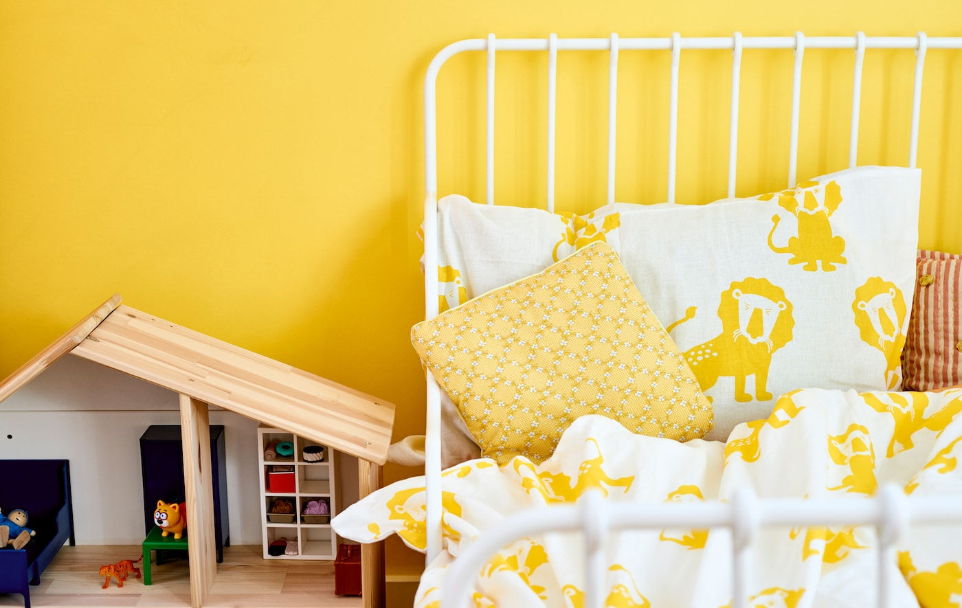 A white bed frame with yellow and white lion print bedding against a yellow wall, next to a wooden doll's house.