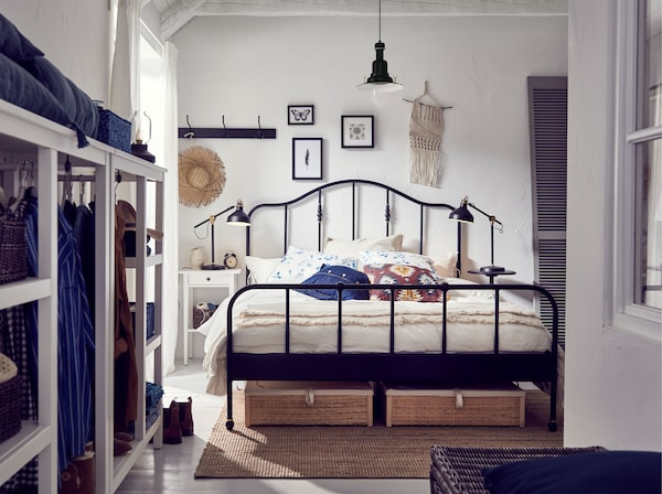 A white bedroom with a black steel IKEA SAGSTUA bed frame, with curved headboard and brass-colour details and storage boxes.