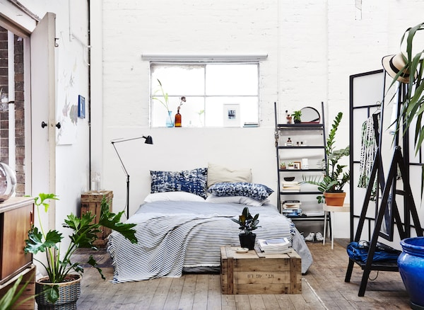 A white bedroom with black and natural wood details.