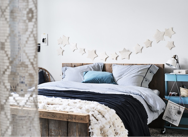 A white bedroom with blue striped bedding.