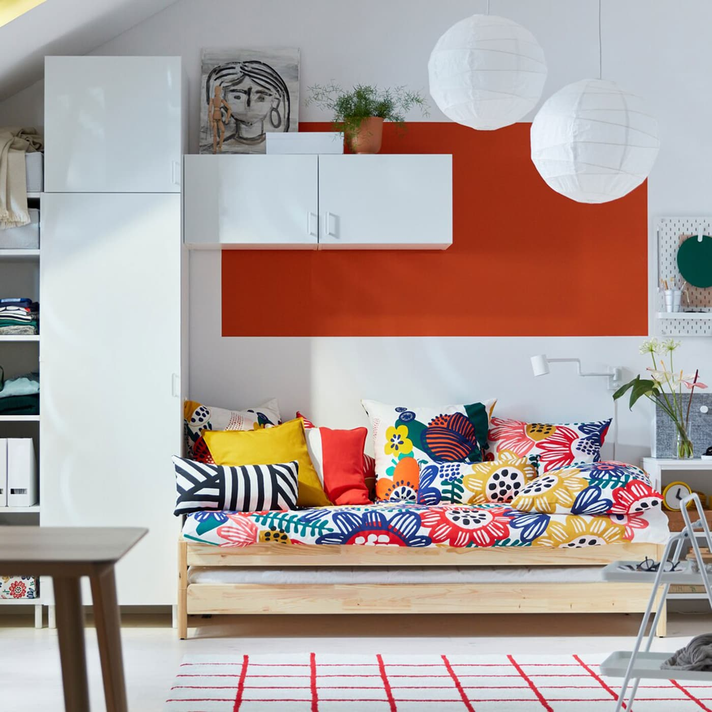A white bedroom with IKEA PLATSA wardrobe solution and SOMMARASTER colourful flower patterned bedsheets.
