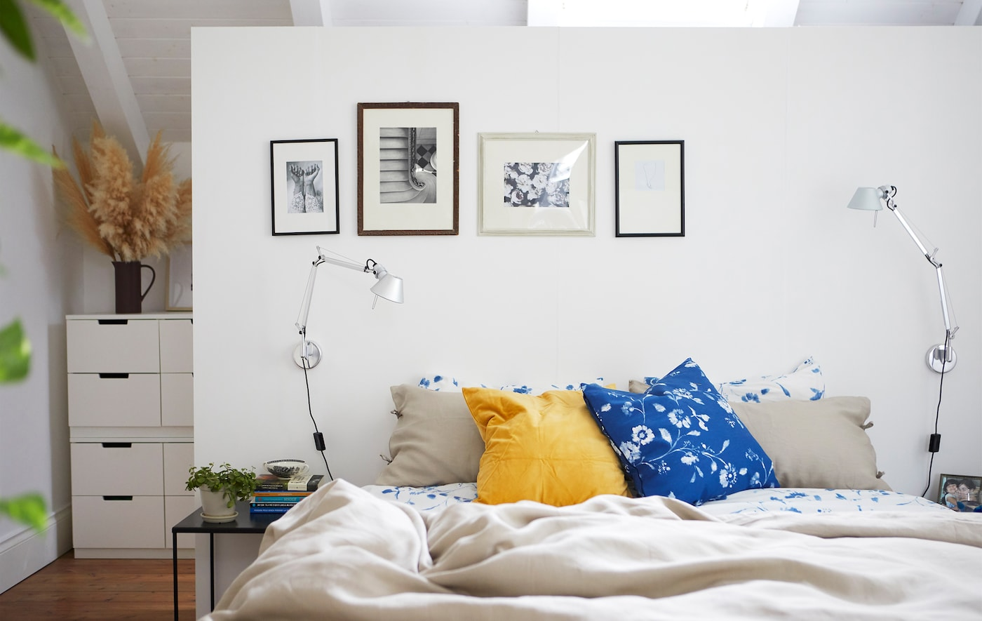 A white bedroom with neutral and floral bedding and black white photos on the wall.