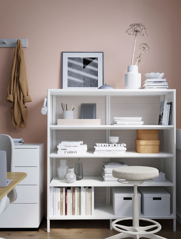 A white BEKANT shelving unit holding books, vases, stationery, headphones and storage boxes. A cream stool is in front.